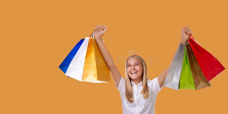 拿着在她的头上的购物妇女购物带来微笑在黄色背景的销售购物期间 库存图片