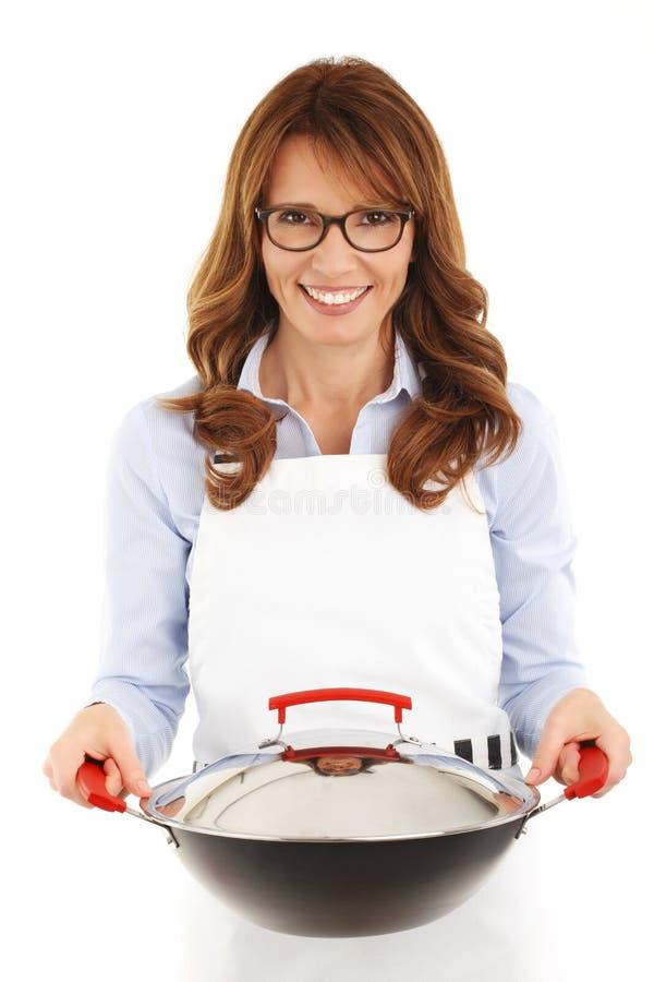 拿着铁锅的俏丽的主妇 库存照片