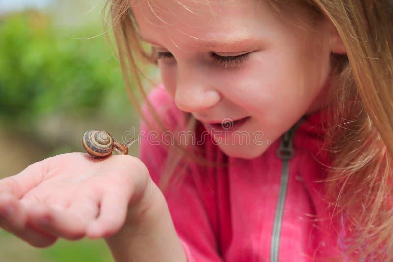 拿着在她的手上的女孩蜗牛 免版税图库摄影