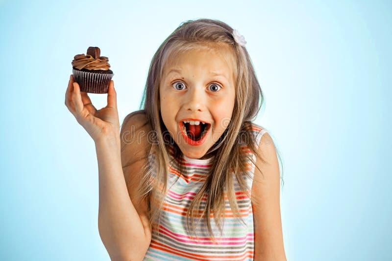 拿着在她的手上的年轻美好的疯狂的愉快和激动的白肤金发的女孩8或9岁多福饼看起来痉挛和快乐在suga 库存照片