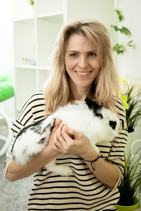 拿着在她的手上的美丽的女孩一只白色兔子 免版税库存图片