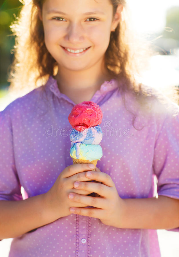 拿着冰淇凌的小smilling的女孩 库存照片