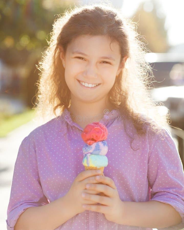 拿着在她的手的Smilling女孩冰淇凌户外 库存照片