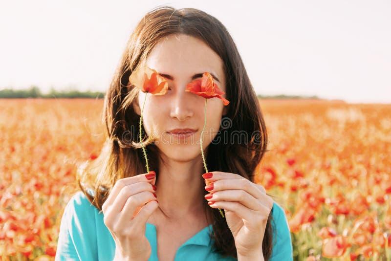 拿着在她的眼睛前面的妇女鸦片 图库摄影