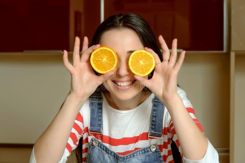 拿着在她的眼睛和微笑前面的主妇橙色切片 免版税库存照片