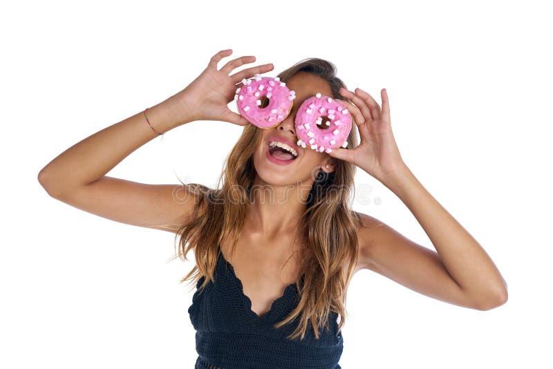 拿着在她的眼睛的青少年的女孩油炸圈饼风镜 免版税图库摄影