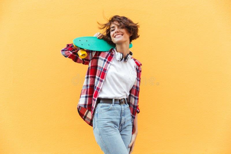 拿着在她的肩膀的快乐的年轻十几岁的女孩滑板 免版税库存照片