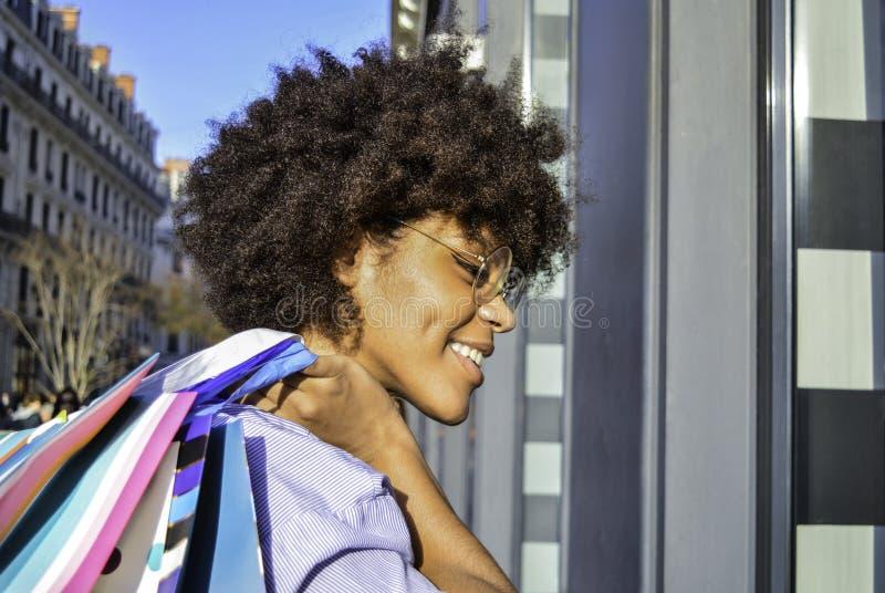 拿着在她的肩膀的美丽的微笑的年轻黑人妇女购物带来 关于购物、生活方式和peopl的概念 免版税图库摄影