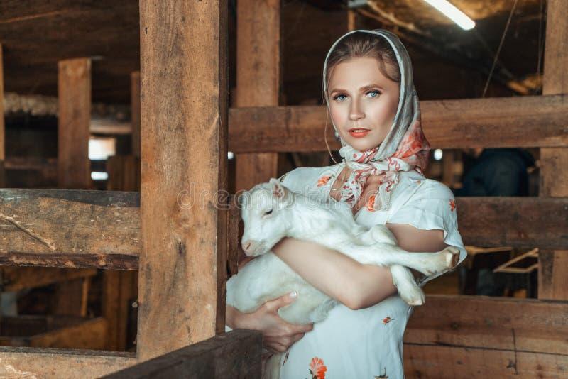 拿着在她的胳膊的农场的Feshion妇女一只小的山羊 免版税库存照片