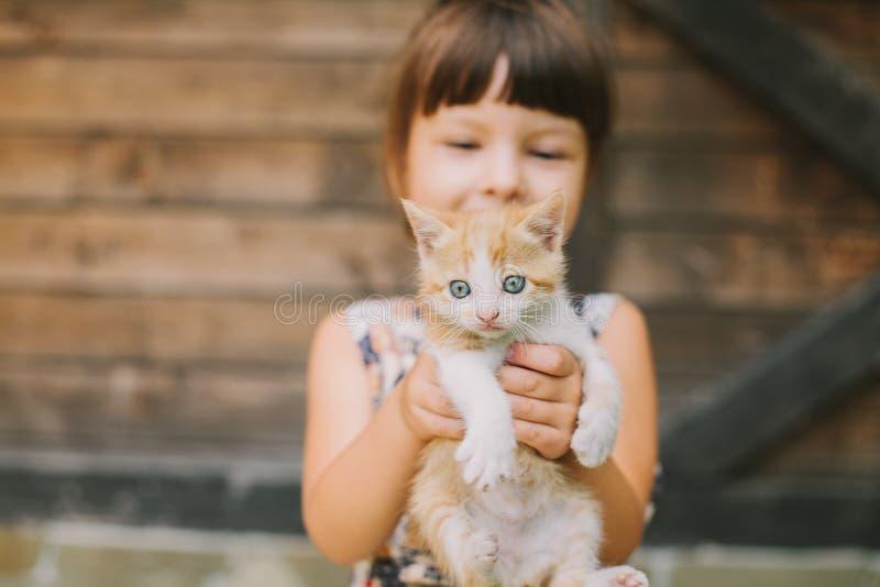 拿着在她的胳膊的快乐的小女孩一只猫 免版税图库摄影