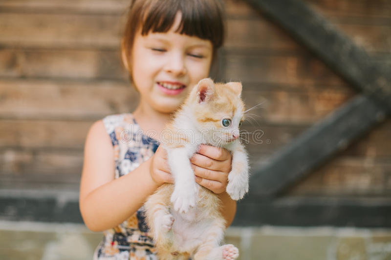 拿着在她的胳膊的快乐的小女孩一只猫 库存图片