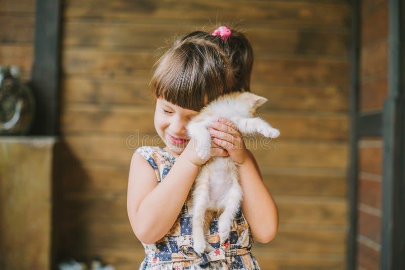 拿着在她的胳膊的快乐的小女孩一只猫 免版税库存图片
