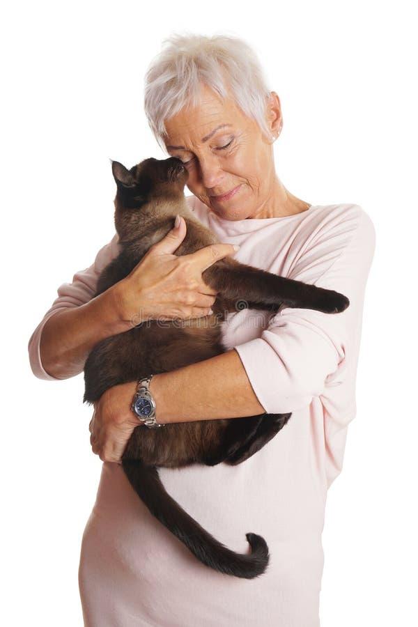 拿着在她的胳膊的成熟妇女猫 库存图片