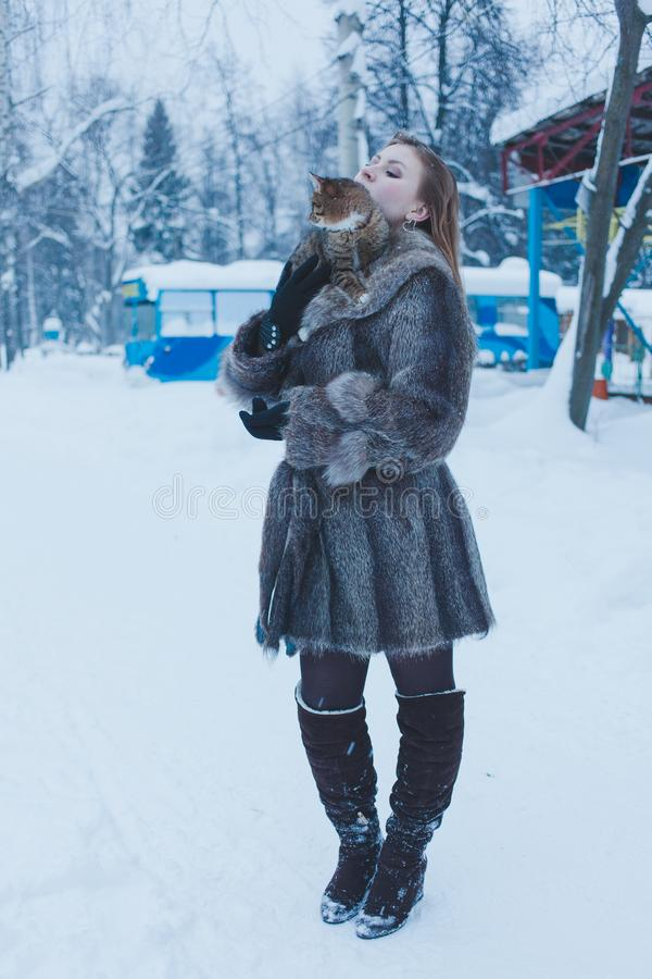 拿着在她的胳膊的毛皮大衣的女孩一只猫以冬天森林为背景 免版税图库摄影