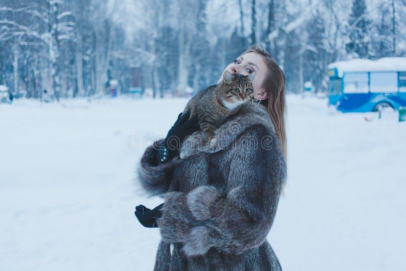 拿着在她的胳膊的毛皮大衣的女孩一只猫以冬天森林为背景 免版税库存图片
