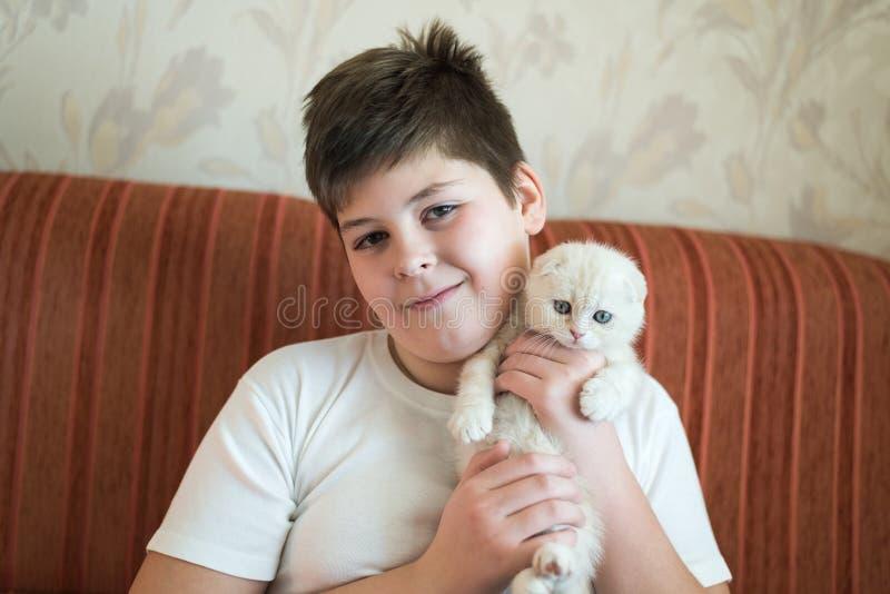 拿着在她的胳膊的男孩少年小猫 免版税库存图片