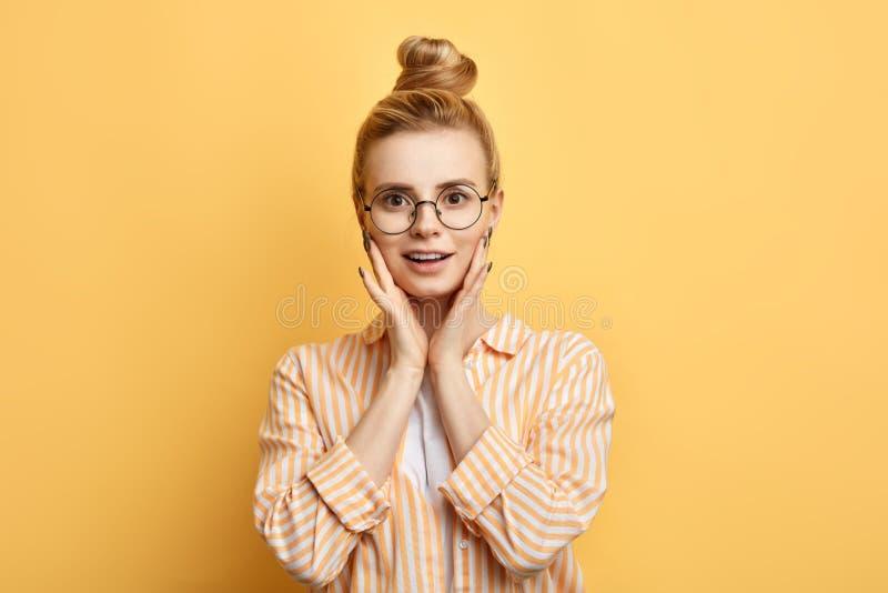 拿着在她的面颊的Attrctive时髦的女生棕榈 免版税图库摄影