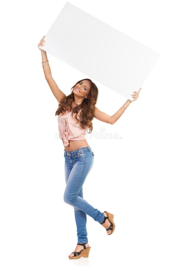 拿着在她的头上的美丽的女孩白色海报 免版税库存图片