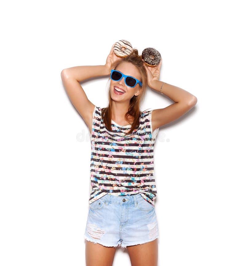 拿着在她的h的太阳镜的嬉戏的女孩油炸圈饼 库存图片