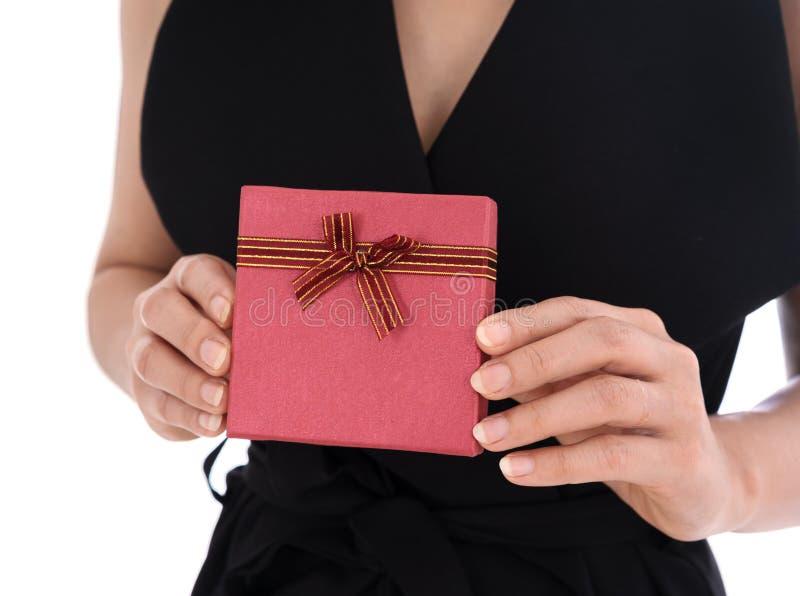 拿着在姿态的妇女一个礼物盒给隔绝在白色背景 免版税库存照片