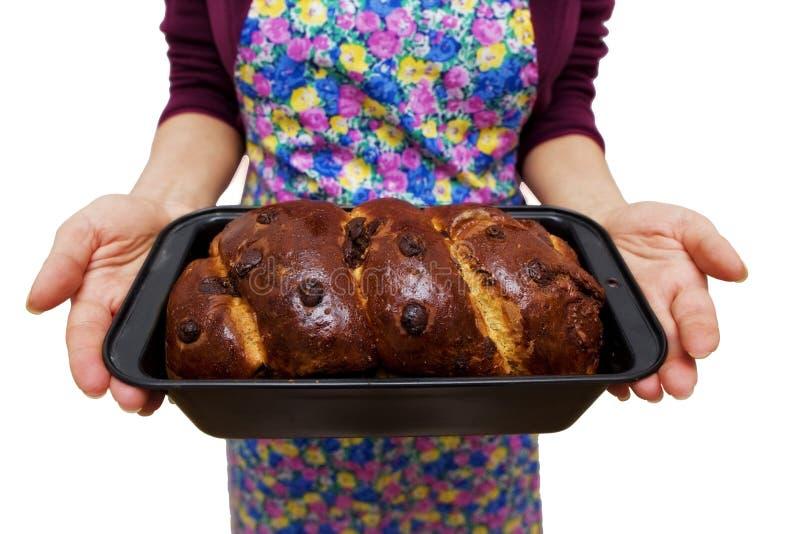 拿着在家做的仍然新近地被烘烤的传统罗马尼亚圣诞节Xmas松糕cozonac以烘烤形式的妇女 免版税图库摄影
