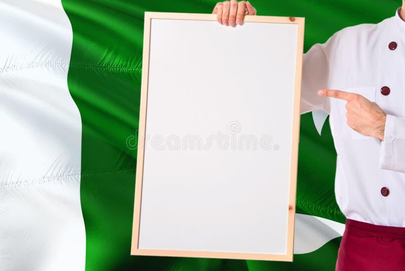拿着在巴基斯坦旗子背景的巴基斯坦厨师空白的whiteboard菜单 烹调指向文本的佩带的制服空间 图库摄影