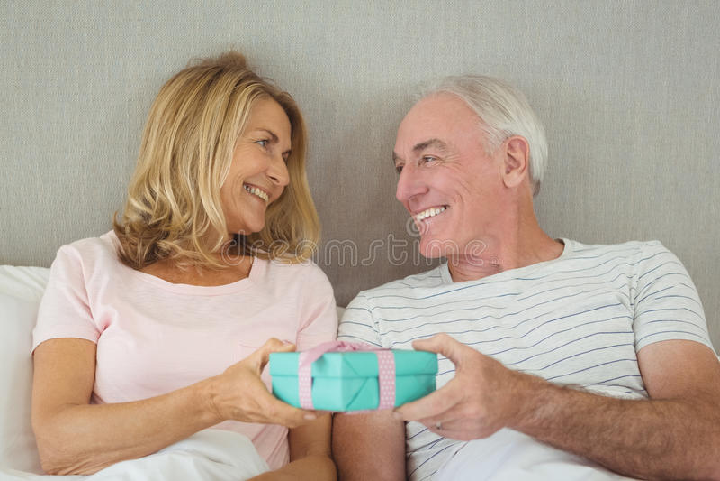 拿着在床上的资深夫妇礼物盒 免版税库存照片
