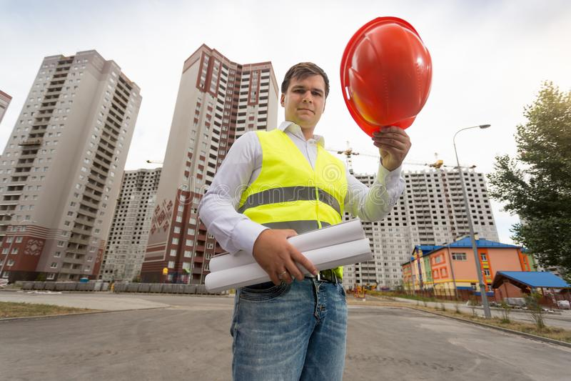 拿着在建筑工地的年轻男性建筑师画象红色塑料安全帽 免版税库存图片