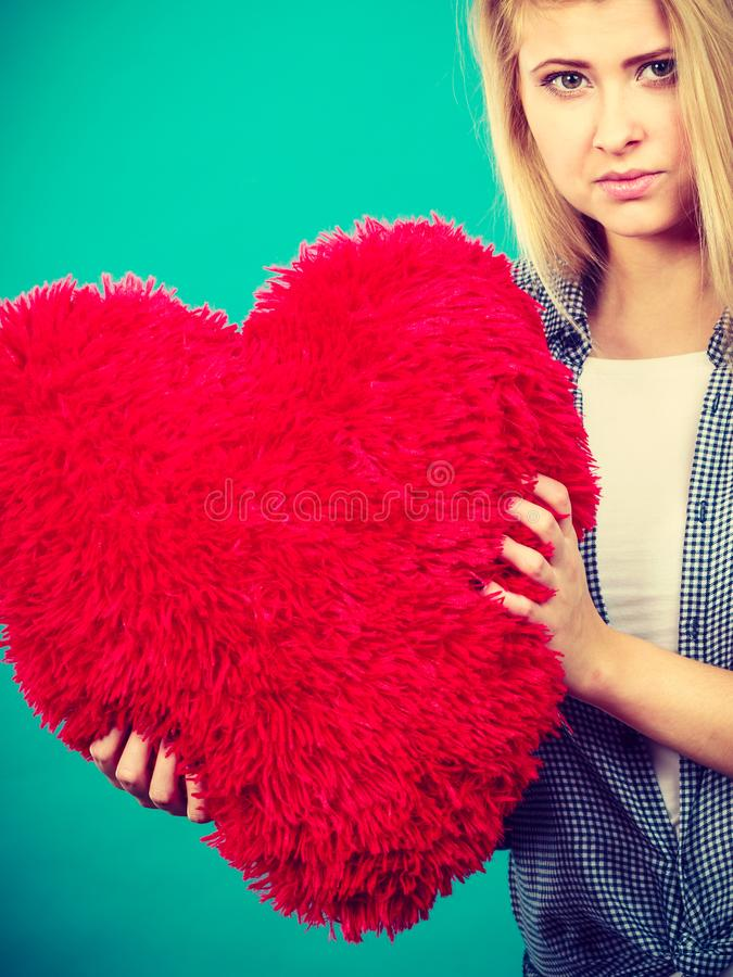 拿着在心脏形状的哀伤的妇女红色枕头 免版税库存照片