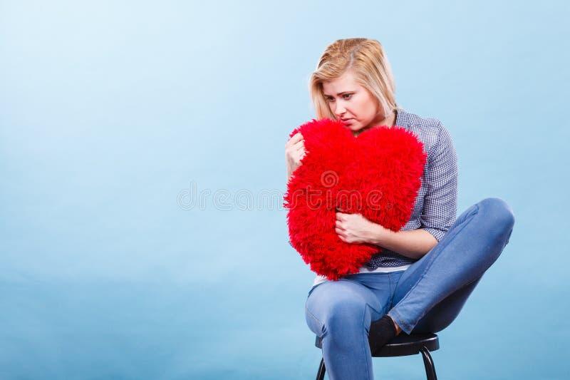 拿着在心脏形状的哀伤的妇女红色枕头 免版税库存图片