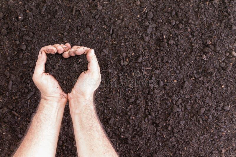 拿着在心脏形状的对手土壤 免版税库存照片