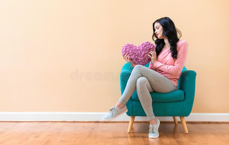拿着在情人节题材的妇女心脏坐垫 免版税图库摄影