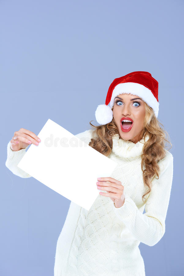 拿着在惊奇面孔的白肤金发的妇女白纸 免版税库存照片