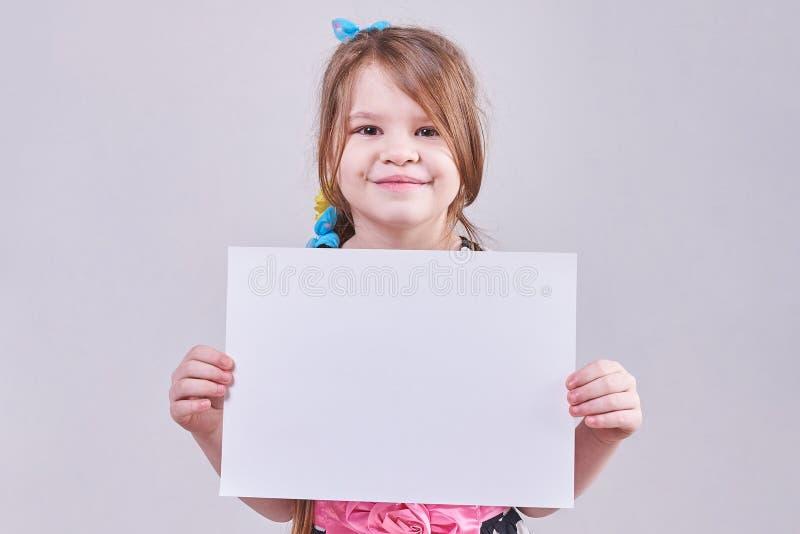 拿着在手上一张白色纸片的美丽的小女孩 图库摄影