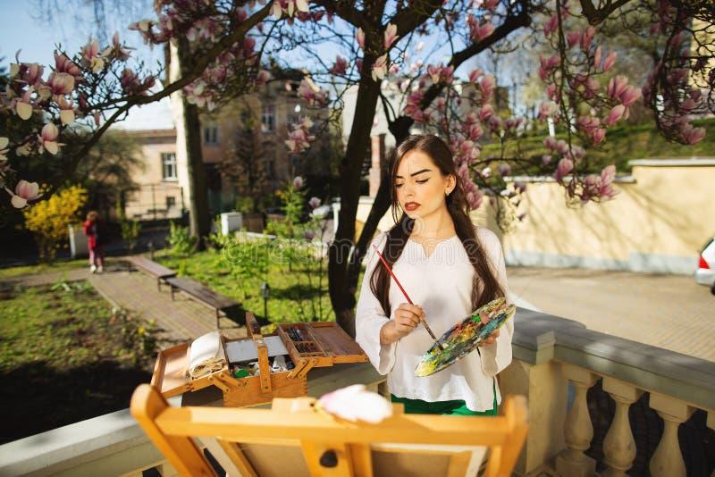 拿着在手上刷子和调色板的年轻深色的妇女艺术家 在她附近木兰树和各种各样的艺术设备 免版税库存图片