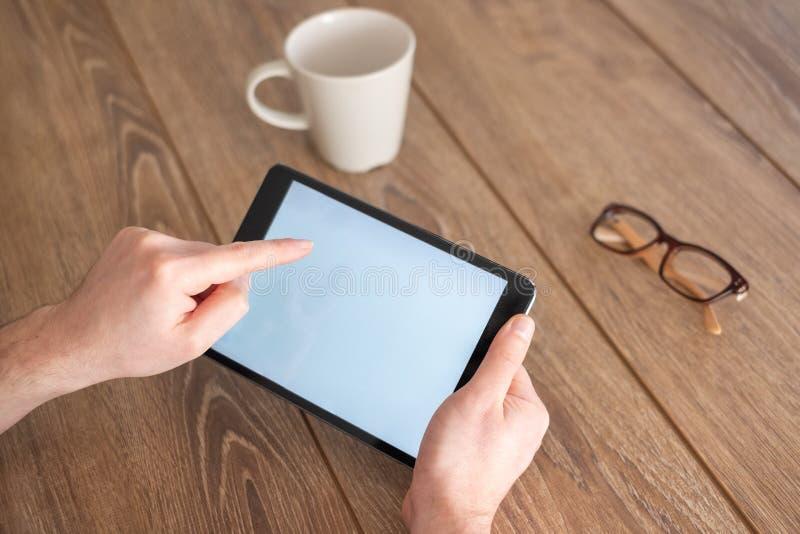 拿着在手上在一张木桌上的一种数字片剂 免版税库存图片