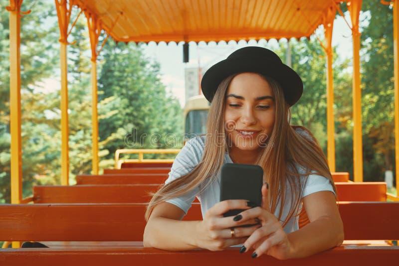 拿着在手smi的时髦帽子的年轻行家女孩智能手机 库存照片