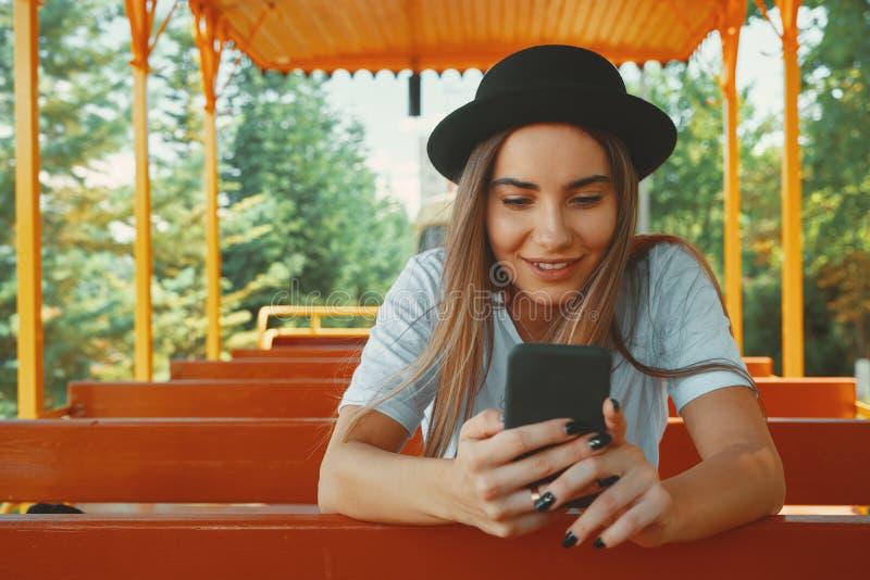 拿着在手smi的时髦帽子的年轻行家女孩智能手机 库存图片