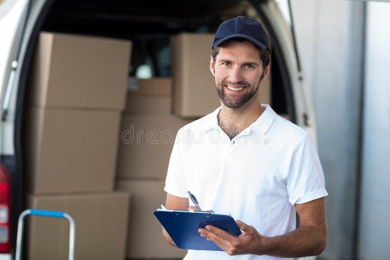 拿着在搬运车前面的送货人画象一张剪贴板 免版税图库摄影