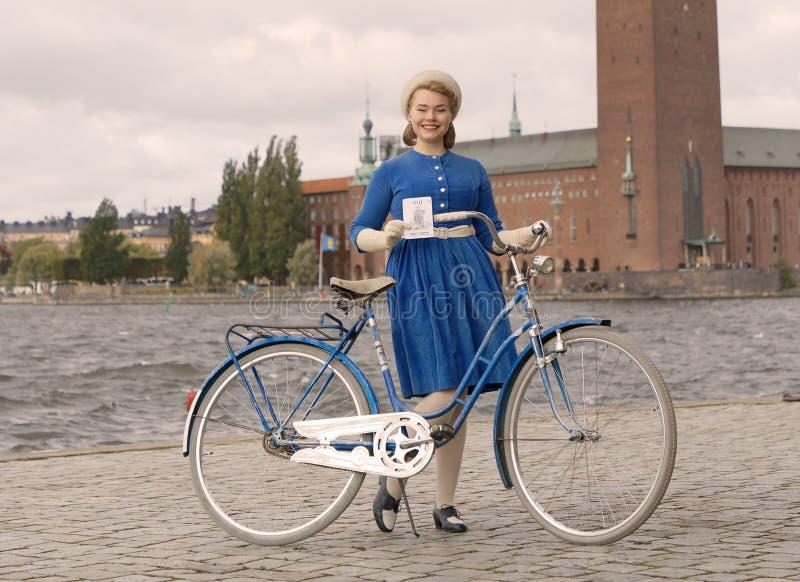 拿着在斯德哥尔摩政府大厦前面的美丽的微笑的妇女佩带的古板的蓝色礼服一辆减速火箭的自行车 免版税库存照片