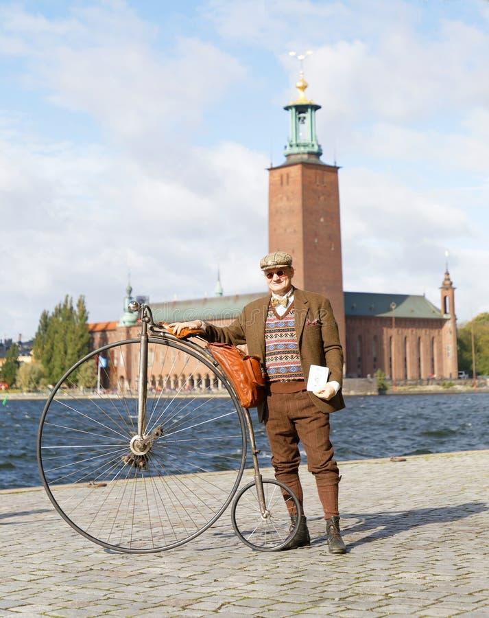 拿着在斯德哥尔摩政府大厦前面的老人佩带的古板的花呢衣服一辆高轮车自行车 库存照片