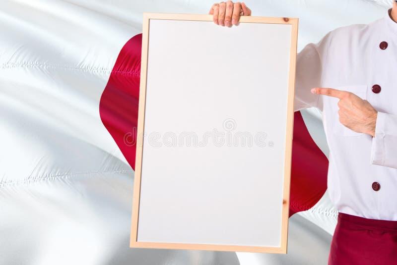 拿着在日本旗子背景的日本厨师空白的whiteboard菜单 烹调指向文本的佩带的制服空间 免版税库存照片