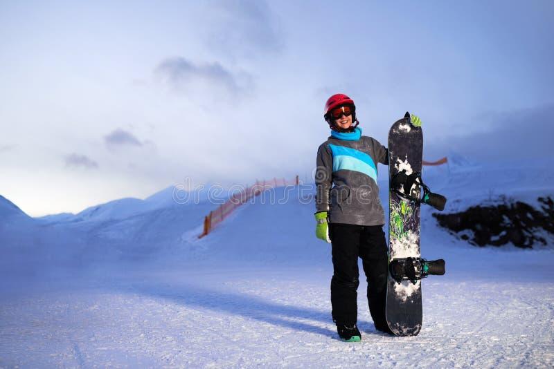 拿着在日落天空和滑雪的女孩一个雪板倾斜 库存图片