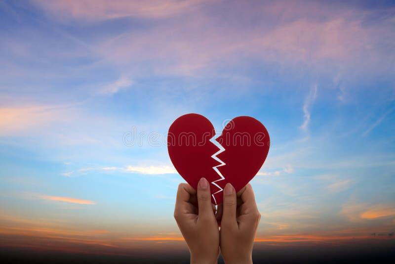 拿着在日落的妇女手被伤的纸红色心 爱、婚礼和情人节概念 免版税库存图片