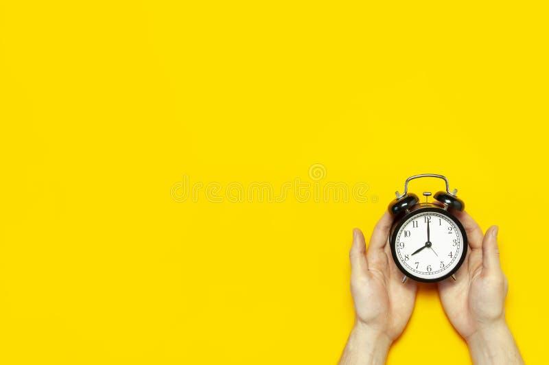拿着在明亮的黄色颜色背景的平的被放置的顶视图男性手黑葡萄酒闹钟与拷贝空间 创造性的时间 库存照片
