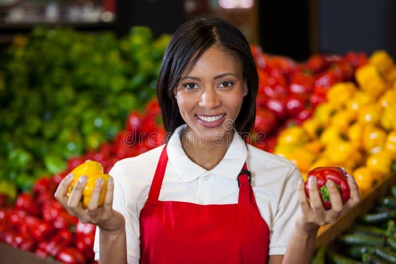 拿着在有机部分的微笑的女职工甜椒 免版税库存图片