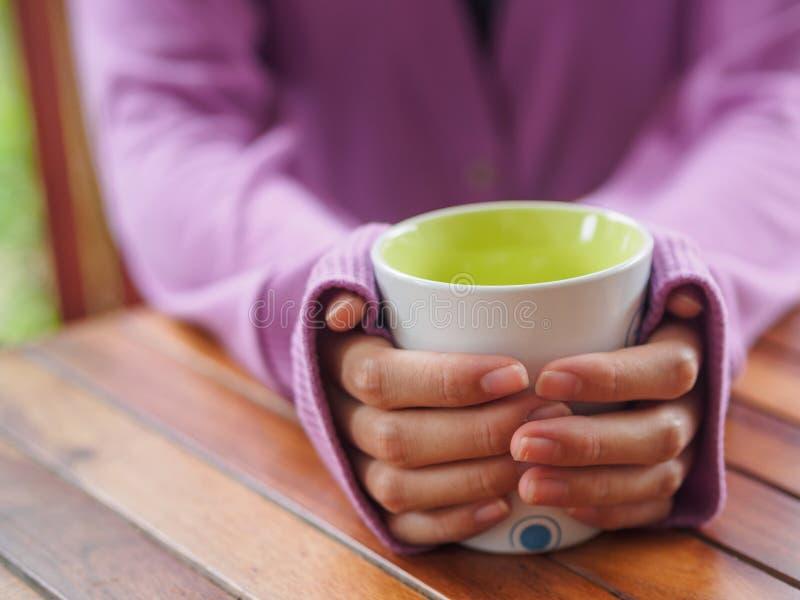 拿着在木桌上的女性手一个杯子 免版税库存图片