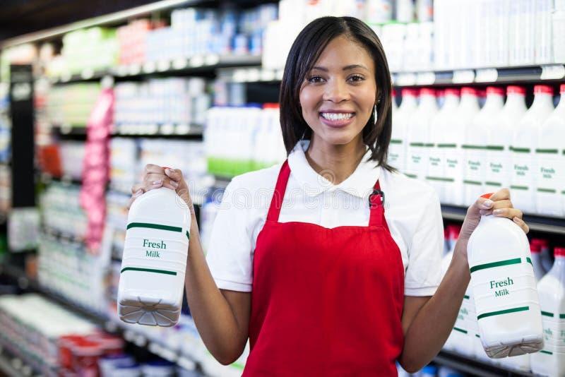 拿着在架子的女职工牛奶瓶 免版税库存照片