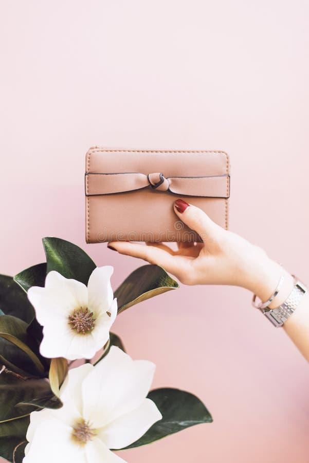 拿着在柔和的淡色背景的女孩一个桃红色钱包与花 免版税库存图片