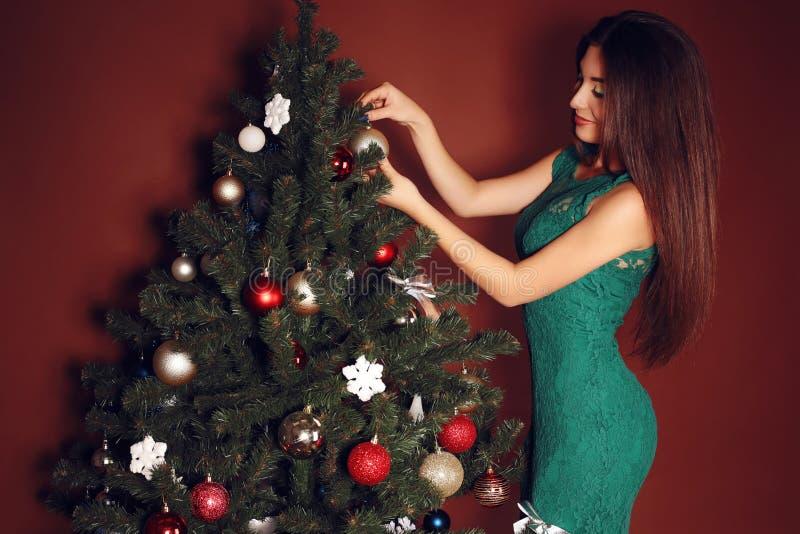 拿着在树的背景的妇女圣诞节球 免版税图库摄影
